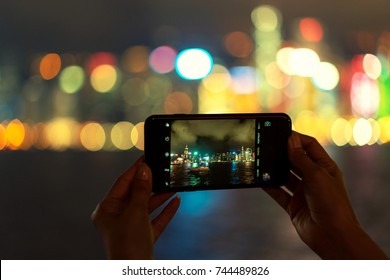 Hand holding mobile smart phone Taking photo with bokeh light background