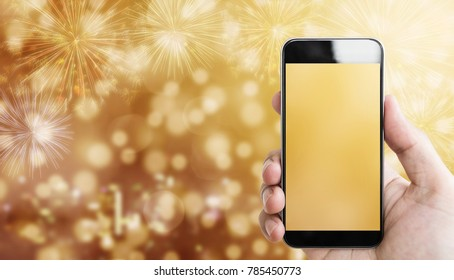 Hand holding mobile smart phone, luxury gold Bokeh light with fireworks background