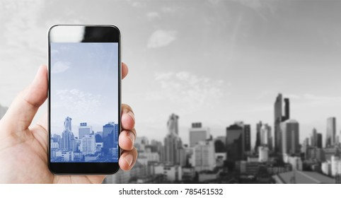 Hand holding mobile smart phone, black and white city background