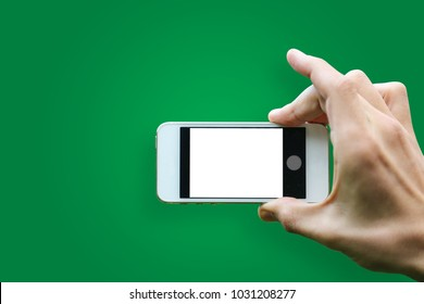 Hand holding mobile smartphone with blank screen horizontally on green background