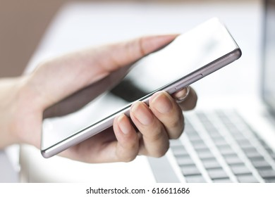 Hand holding mobile smartphone with blank screen. A smartphone is a mobile or cellular phone that runs off a mobile operating system and functions like a mini computer .