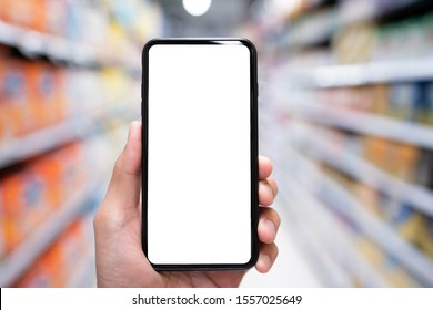 Hand holding mobile smartphone empty touch screen on supermarket or convenience stores background.Blank free word,Copy space for text.Use for your advertisement design or mock up text.Business concept