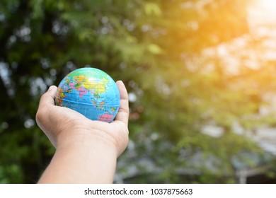 Hand holding model globe on green tree background.