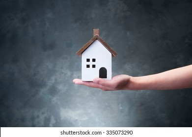 Hand holding a model of house