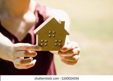 Hand holding a model of house.Hands of family holding model of house. toy house in hands.