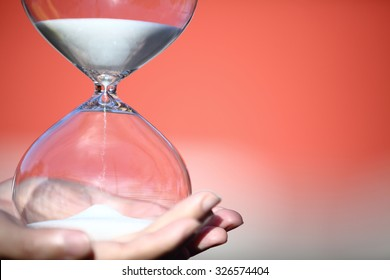 Hand holding a modern hourglass -- sand trickling through the bulbs of a crystal sand glass. symbol of time. countdown. Time Management. Hourglass timer concept for business deadline and leadership