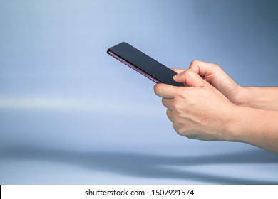 Hand holding Modern mobile smart phone with black screen for mockup on Blue background . Close-up of hands sliding using smartphone are shopping and searching or Selfie on social networks concept  .