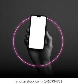 Hand holding modern smartphone with a blank white screen and neon light glow