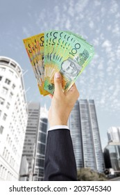 Hand holding money - Australian dollars (AUD) - on building background