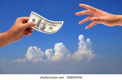 hand holding money dollars, 100 US dollar banknote on sky-clouds background.