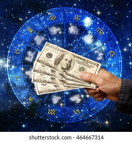 hand holding money in front of a zodiac chart, concept for astrology and money, earning with astrology