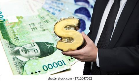 Hand holding Money symbol shape on Stacked of South Korea won money bills