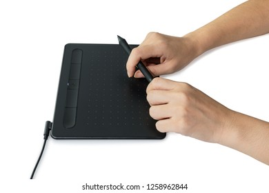 Hand holding mouse pen on the digital graphics tablet with isolated on white background, clipping path included. Graphic designer working concept. Selective focus.