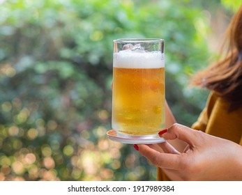 Hand holding a mug of beer at a party in the garden background. Close-up photo. Space for text. Concept of party and beverages.