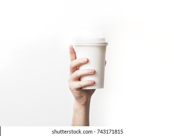 Hand holding a mug,  Paper Coffee Cup  with delicious coffee in a cafe on a white background, mock up, blank, your cafe shop design