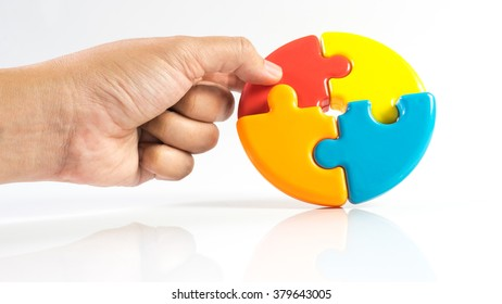 Hand holding multicolour pie chart or pieces of puzzle. Concept of process solution and teamwork collaboration. Isolated on white background. Slightly de-focused and close-up shot. Copy space.