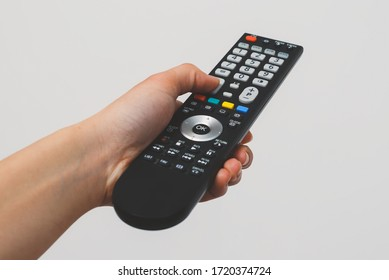 Hand holding Multimedia remote control on white background.