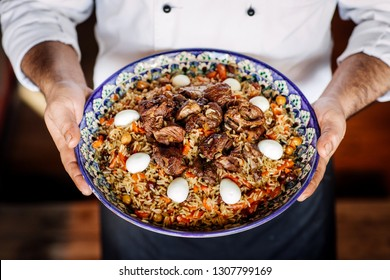 hand holding national dish of uzbek pilaf with vegetables, meat and eggs