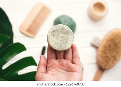 Hand holding natural solid shampoo bar on background of bamboo brush, deodorant, sponge on white wood with green monstera leaves. Zero waste. Choice plastic free eco products
