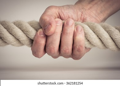 Hand holding nautical rope in close-up. Symbol of power, strength and effort.