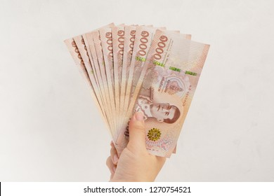Hand holding new 1000 Thai Baht banknotes on white wall background. Business and finance concept.