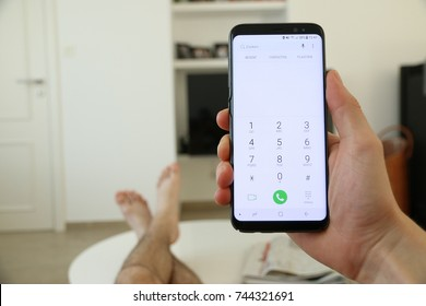 A hand holding a new cellphone, which displays the numeric dial pad on the touch screen. In the background, the legs of the person who's sitting in the sofa, are laying on a white living room table.