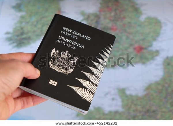 Hand holding a New Zealand NZ passport in front of a map of Europe.
