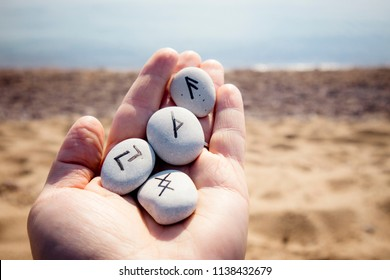 Hand holding norse rune stones with black symbols for fortune telling, beautiful outdoor sunny sandy beach with sea on background.