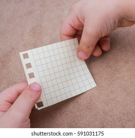 Hand holding a note paper on a brown background