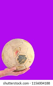 Hand holding old and weathered soccer ball on a purple background