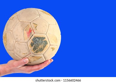 Hand holding old and weathered soccer ball on a blue background