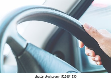 Hand holding on black steering wheel while driving in the car