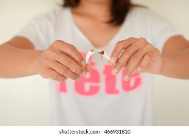 hand holding on broken cigarette with blurred woman act stop smoking background.