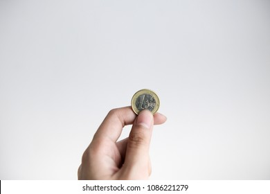 A hand holding one euro coin with white background
