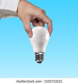 Hand holding one LED bulb, isolated on blue background. Energy saving concept.