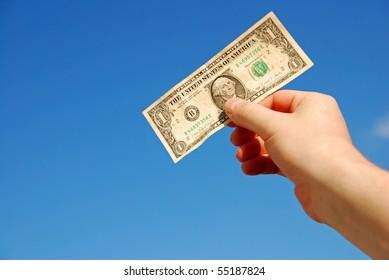 hand holding one US dollar against blue sky