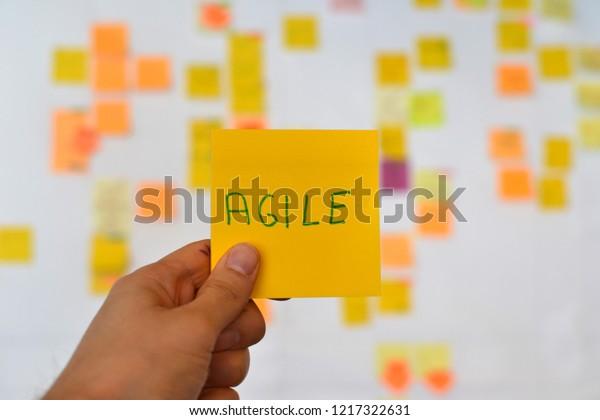 Eine Hand hält einen orangefarbenen agilen Aufkleber und es gibt ein Kanban-Board agiler Methodik auf dem Hintergrund, was eine sich entwickelnde Tendenz im IT-Geschäft ist.