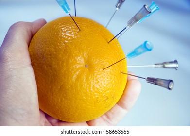 Hand holding an orange with multiple syringe needles - pin cushion.
