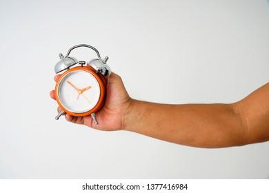 Hand holding an orange vintage alarm clock isolated on white background