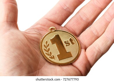 Hand holding out a 1st place gold badge isolated on a white background