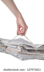 Hand holding a pack of newspaper for recycling