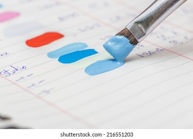 a hand holding paint brush to note on the paint note
