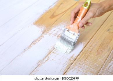 Hand holding paint brush and painting on wood wall with white color