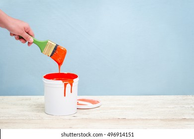 Hand holding the paint brush and White plastic bucket with red color on wood,vintage background