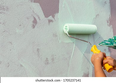 Hand holding a paint roller on the cement wall.