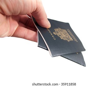A hand holding a pair of Canadian Passports, isolated on white.