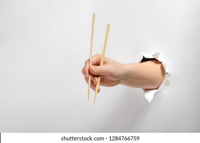 Hand holding pair of wooden chopsticks through torn white paper background. Cutlery, Asian eating culture.