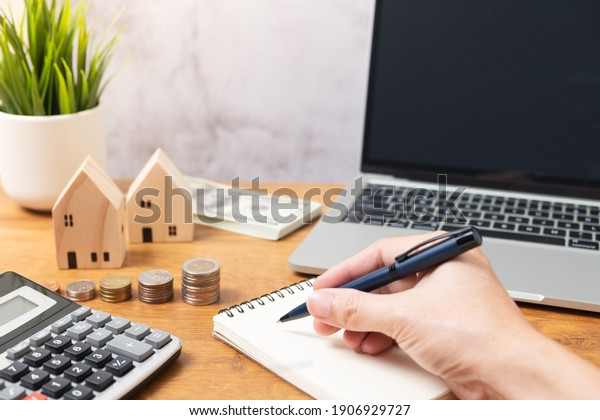 Hand holding pan with stacking Coins and wooden house model or real estate concept. Real estate broker. insurance or loan real estate. business house investment idea.