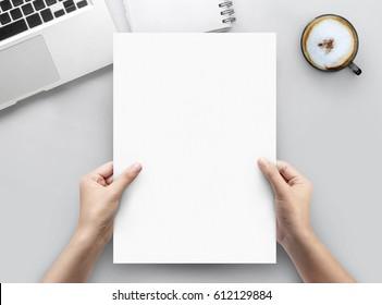 Håndholdningspapir a4 på hvitt kontorbordbordsoversikt med kopieringsplass