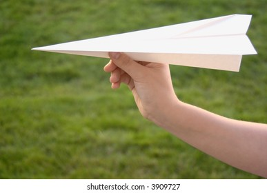Hand holding a paper airplane with grassy background